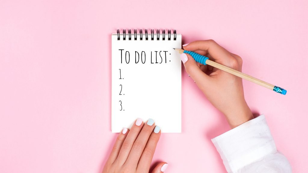 A woman writing a to do list