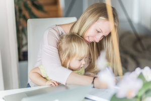Woman working from home with a child on her lap