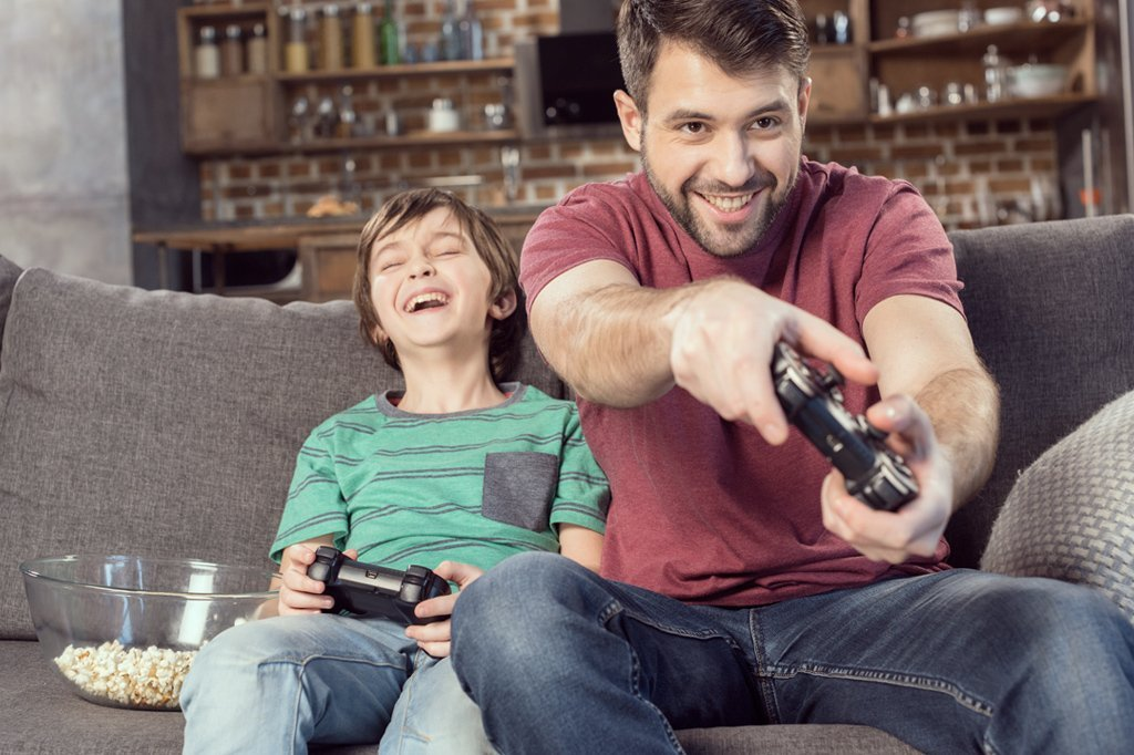 A son and dad playing video games