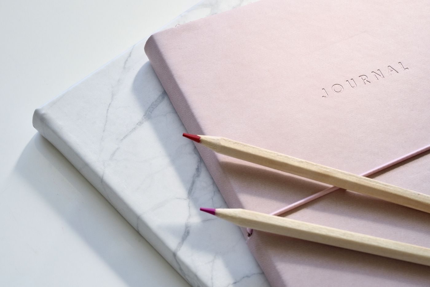 A pastel pink journal with a pen on it